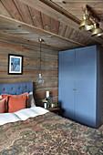 Blauer Kleiderschrank im rustikalen Schlafzimmer im Blockhaus