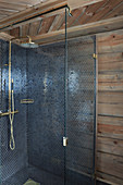 Blue mosaic tiles and golden shower fittings in shower cabin in log cabin