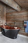 Free-standing copper bathtub in bathroom of log cabin