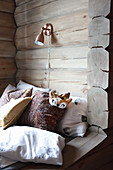 Furry sleeping mask and scatter cushions in cubby bed in log cabin