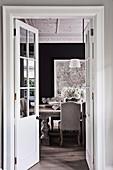 Blick durch offene Doppeltür ins elegante Esszimmer in Grautönen