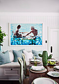 Photo picture over wooden sofa, dining table with decorative cactus in the foreground