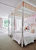 Two white saddle bed with saddle pads in bedroom with soft pink walls and curtains