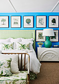 Picture gallery with natural motifs on a bright blue wall above a double bed