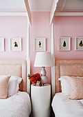 Round side table between two post beds in pink bedroom