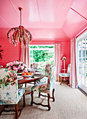Dining room with pink wall and ceiling, round dining table and upholstered chairs with floral motifs