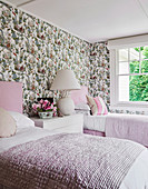 Two white and pink single beds against a wall with floral pattern wallpaper