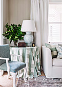 Round side table with checkered tablecloth between antique upholstered chair and sofa