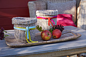 Candle lanterns with knitted covers and apples on wooden tray