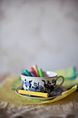 Colourful chalks in cup on crumpled paper
