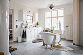 Spacious country-house-style bathroom with vintage-style free-standing bathtub