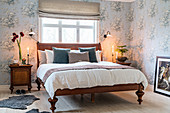 Antique wooden bed in bedroom with romantic, pale-blue floral wallpaper