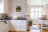 Spacious, white country-house kitchen in renovated manor house