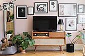 TV on top of retro radio below gallery of pictures on pink wall