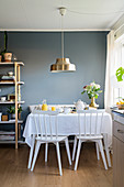 Set breakfast table in front of blue-grey wall in dining room