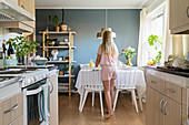 Girl wearing pyjamas setting breakfast table in open-plan kitchen-dining room