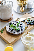 Bowl of whipped cream next to flat cake decorated with blueberries and lemon balm