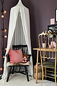 Chair under canopy in child's bedroom with purple walls