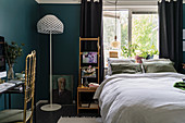 Mystical colour scheme in bedroom with deep teal walls