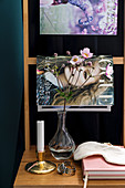 Magazines and vase of Japanese anemones arranged on ladder-back chair used as bedside table