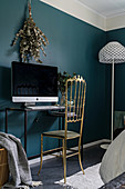 Golden chair in front of computer on console table against deep teal wall