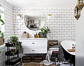 White, Bohemian-style bathroom with subway tiles, floating washstand and free-standing bathtub