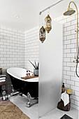 Milchglas-Trennwand zwischen freistehender schwarzer Badewanne und Duschbereich