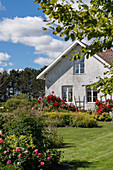 Lawns and blooming summer garden of white country house
