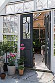 Offene Doppeltür zum romantischen Gartenhaus aus alten Fenstern