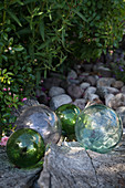 Charming arrangement of glass balls and pebbles in garden