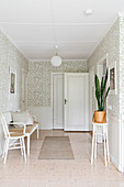 Chair, bench and houseplant in bright wallpapered hallway