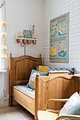 Wooden bed and patterned wallpaper in nursery
