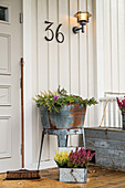 Plants in metal tub next to front door with house number and sconce lamp