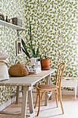 Sewing machine on wooden table, chair and leaf-patterned wallpaper in bright room