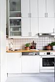 White fitted kitchen with white-tiled splashback