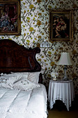 Rustic wooden bed with pillows, bedside table and paintings on wallpapered wall in bedroom