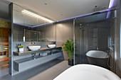 Doppelwaschtisch mit Aufsatzbecken, Duschkabine mit Glasabtrennung und Badewanne im Designerbad