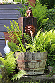 Ferns around tub below waterspout and ornaments in garden
