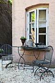 Mediterrane Metall-Gartenmöbel auf gekiester Terrasse am Haus