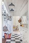 Diele mit Schachbrettfliesen, Fotogalerie und weißes Treppengeländer