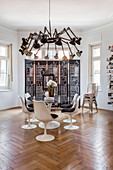 Deckenleuchte mit Gelenklampen überm Designertisch im Altbau