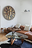 Old church clock face, leather sofa and designer table