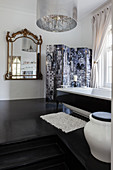 Baroque mirror in bathroom with steps leading to free-standing bathtub