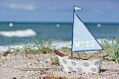 Small toy sailing boat on beach