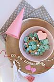 Stillleben mit Bonbons, Spitztüte und Buchstabenkette auf einem Teller