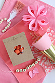Romantic arrangement in pink with string of lettered beads and bag of sweets