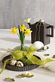 Narcissus in vase with green bow on table