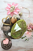 Romantic spring arrangement in natural shades and pink with moss egg