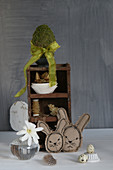 Stitched Easter bunnies in front of ornaments on small set of shelves