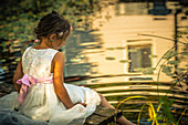 Girl in white summer dress sitting on jetty next to idyllic pond
